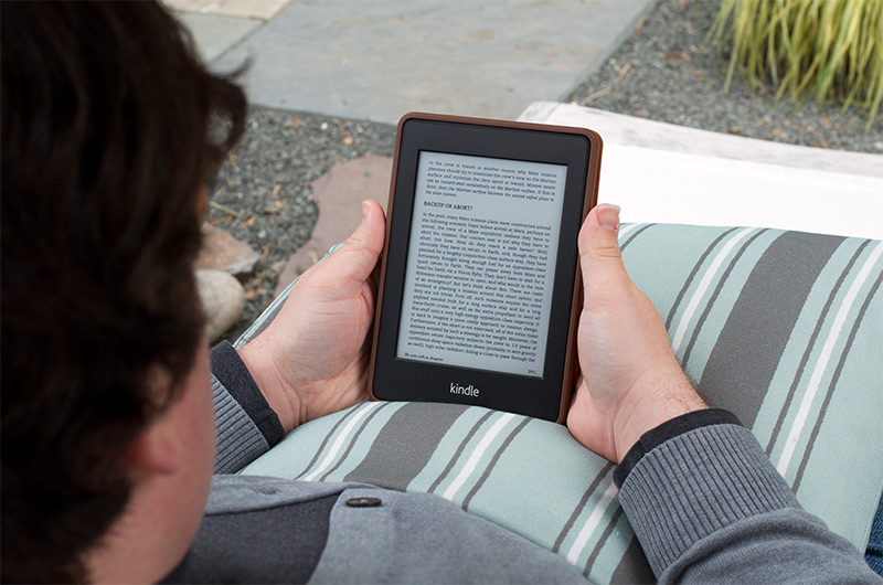 A photo of the author reading a Kindle Paperwhite.